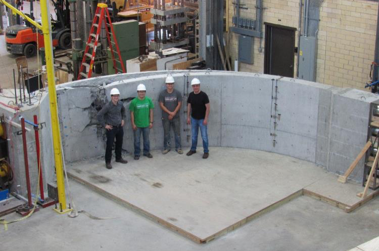 curved concrete structure with 4 men standing in front