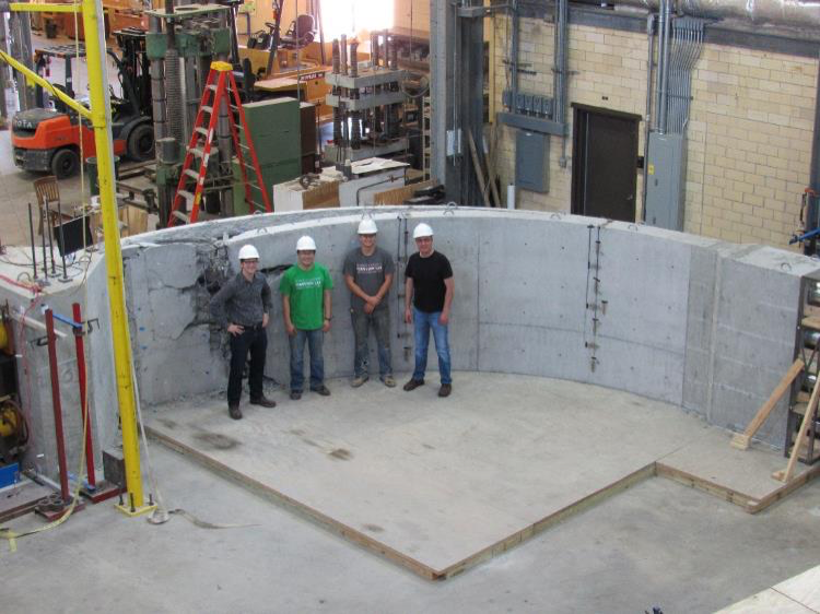 4 men in hardhats in front of curved concrete structure